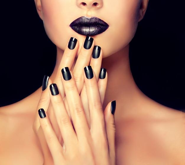 Piękna dziewczyna pokazuje czarny manicure na paznokciach przed dobrze wymodelowanymi ustami pomalowanymi na czarno. makijaż, kosmetyki i manicure.