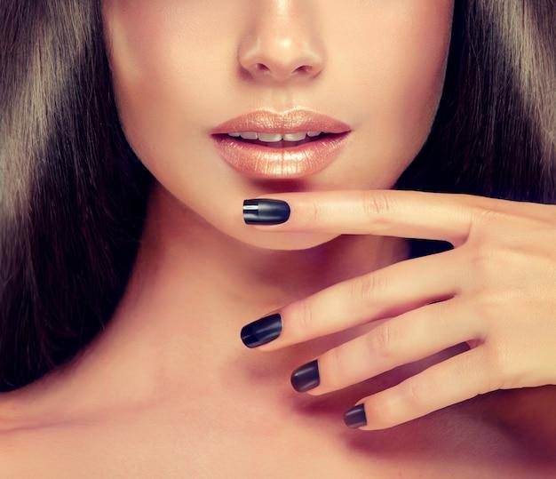 Piękna dziewczyna pokazuje czarny manicure na paznokciach przed dobrze wymodelowanymi ustami pomalowanymi na różowo.