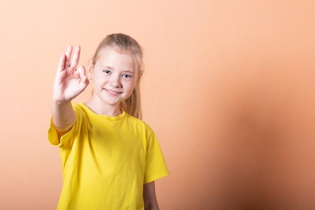 Piękna dziewczyna pokazuje znak porządku na jasnopomarańczowym tle. w dowolnym celu.