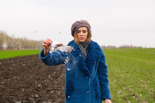 Piękna dziewczyna pozostaje na zewnątrz w niebieskim płaszczu na otwartym polu, pali biały papier, a popiół lata z wiatrem