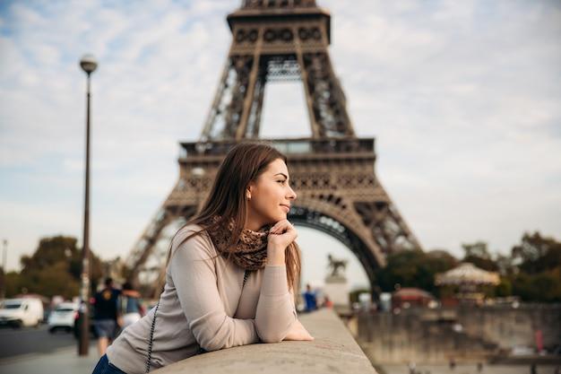 Piękna dziewczyna pozuje do fotografa na tle wieży eiffla. jesień