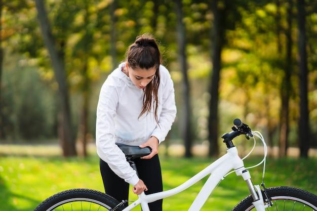Piękna dziewczyna pozuje na białym rowerze. spaceruj na łonie natury.