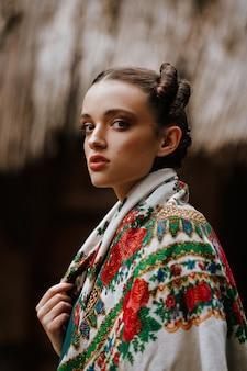 Piękna dziewczyna pozuje w haftowanej sukni