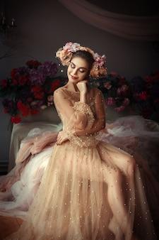 Piękna dziewczyna pozuje w pokoju pełnym kwiatów