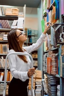 Piękna dziewczyna pracownik biblioteki układa książki na półkach