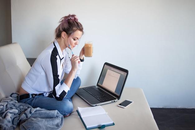 Piękna dziewczyna pracuje w domu z laptopem