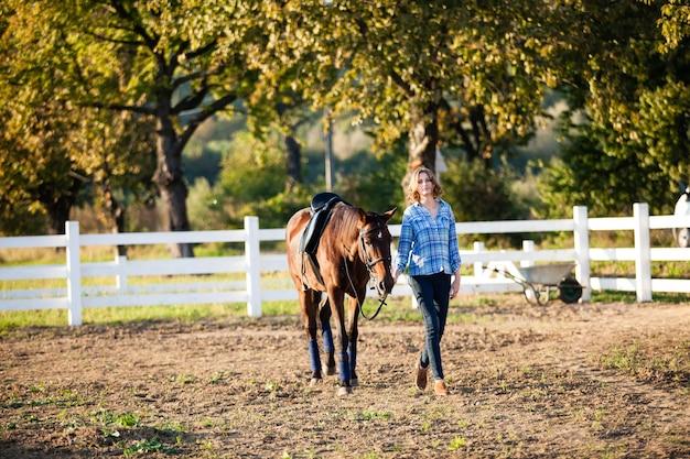 Piękna dziewczyna prowadzi swojego brązowego konia na farmie