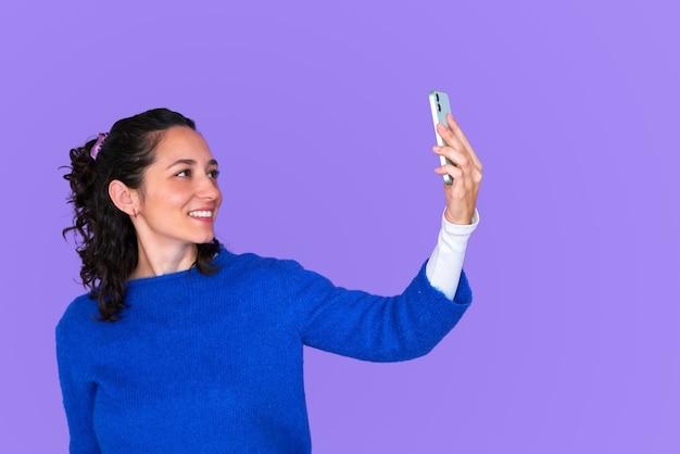 Piękna dziewczyna przy selfie na na białym tle fioletowym tle na sobie niebieski sweter. trzymając smartfon jedną ręką, uśmiechając się do kamery. kręcone włosy.