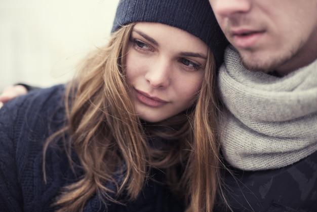 Piękna dziewczyna przytula swojego chłopaka zimą