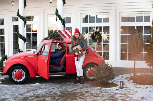 Piękna dziewczyna rasy kaukaskiej w ciepłych zimowych ubraniach niesie mężowi pudełka z prezentami świątecznymi w czerwonym samochodzie