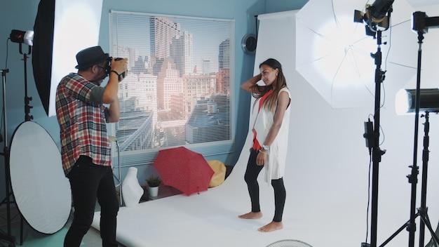 Piękna dziewczyna rasy mieszanej pozuje do fotografa w profesjonalnym studio sesji zdjęciowej