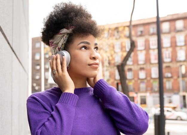 Piękna dziewczyna rasy mieszanej z afro włosami, słuchając swojej ulubionej muzyki
