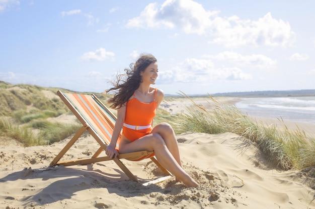 Piękna dziewczyna relaksuje na plaży, siedzi na leżaku