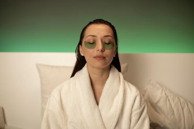 Piękna dziewczyna relaksuje w domu z mokrym włosy siedzieć w łóżku w białym szlafroku