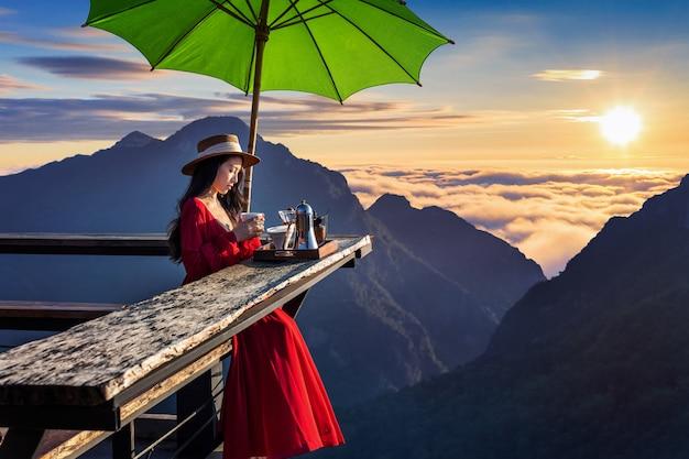 Piękna dziewczyna robi drip kawę w punkcie widokowym wschodu słońca w wiosce pha hi w prowincji chiang rai w tajlandii