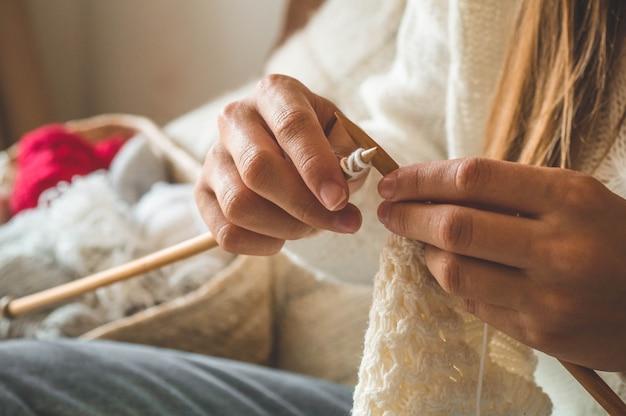 Piękna dziewczyna robi na drutach ciepły sweter na łóżku. robienie na drutach jako hobby. akcesoria do dziania.