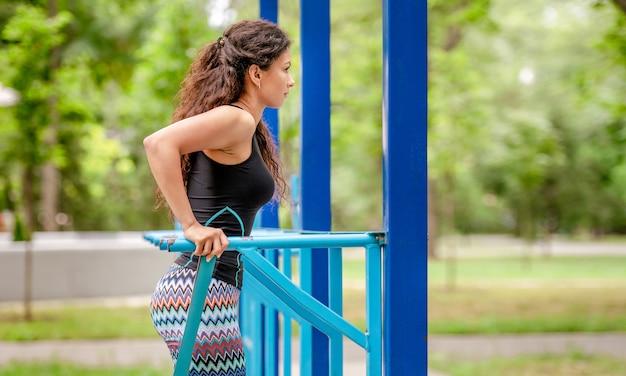 Piękna dziewczyna robi pompki na stadionie podczas treningu ramion. młoda sportowa kobieta, ćwiczenia na świeżym powietrzu