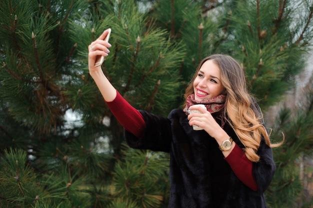 Piękna dziewczyna robi selfie w jesień parku