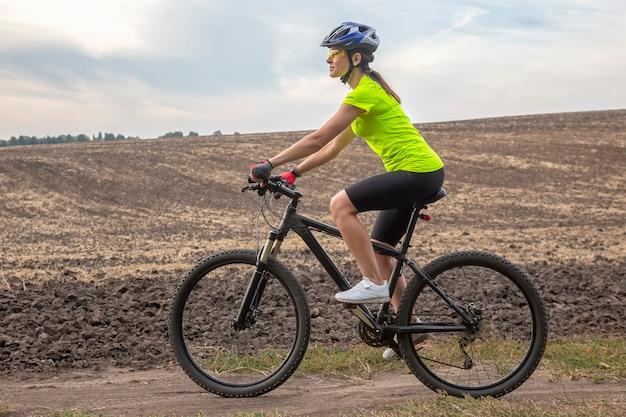 Piękna dziewczyna rowerzysta jeździ na rowerze na polu. zdrowy styl życia i sport. wypoczynek i hobby