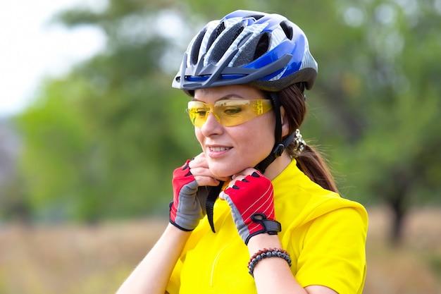 Piękna dziewczyna rowerzysta na żółto w kasku. sport i rekreacja.