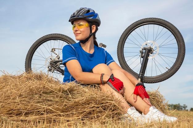 Piękna dziewczyna rowerzysta siedzi na suchej trawie na tle roweru. natura i człowiek