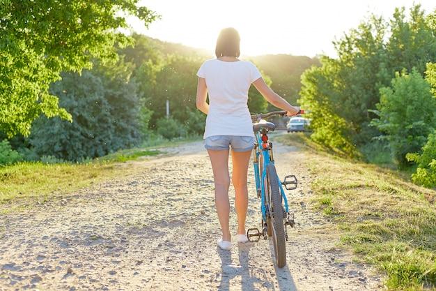 Piękna dziewczyna rowerzysta z rowerem na drodze w kierunku zachodu słońca. hobby i sport