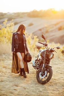 Piękna dziewczyna rowerzysty w czarnych ubraniach stoi na motocyklu z kaskiem w ręce.