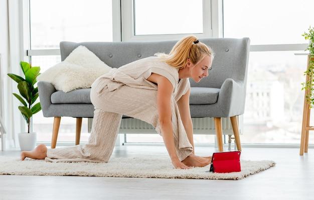 Piękna dziewczyna rozciągnąć swoje ciało podczas zajęć jogi online na tablecie. treningi domowe w czasie pandemii