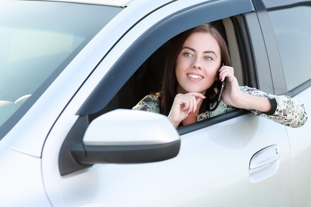 Piękna dziewczyna rozmawia przez telefon jazdy samochodem