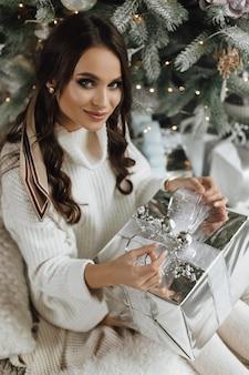 Piękna dziewczyna rozpakowuje prezent w srebrny papier i taśmę