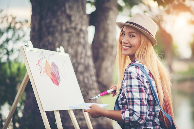 Piękna dziewczyna rysuje obrazek w parku
