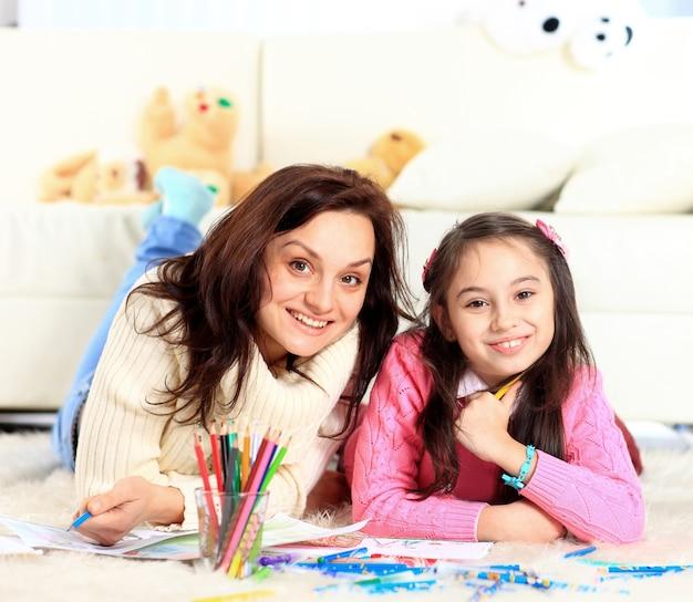 Piękna dziewczyna rysuje z matką