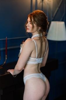 Piękna dziewczyna seksowna brunetka w białej bieliźnie pozowanie w pokoju we wnętrzu
