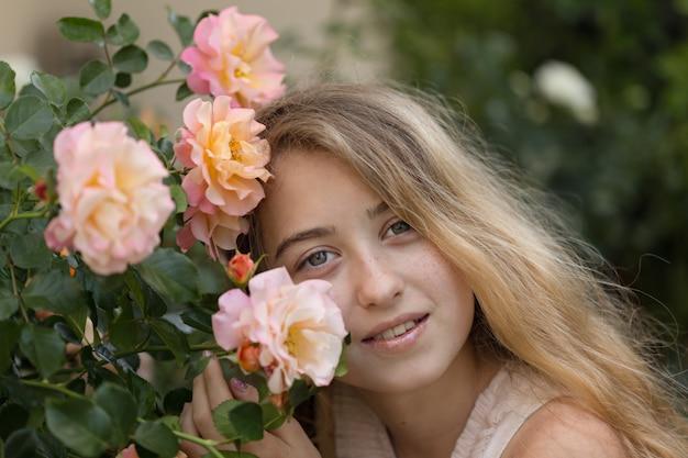 Piękna dziewczyna siedzi i uśmiecha się w pobliżu kwiatów, poza w ciągu dnia.