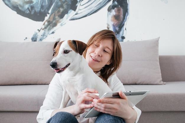 Piękna dziewczyna siedzi na kanapie w domu z tabletem w rękach, obok psa jack russell
