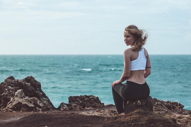 Piękna dziewczyna siedzi na klifie