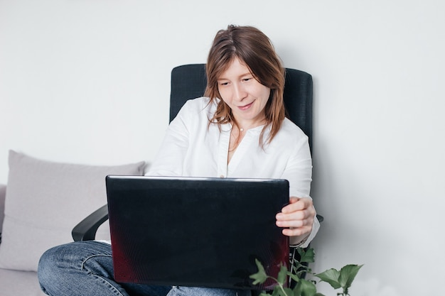 Piękna dziewczyna siedzi na krześle biurowym w domu z laptopem w dłoniach, z pozytywnymi emocjami i pięknym uśmiechem