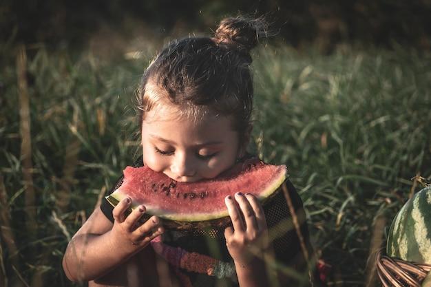 Piękna dziewczyna siedzi na łące z arbuzami. słodkie małe dziecko jedzenie arbuza, siedząc na trawie.