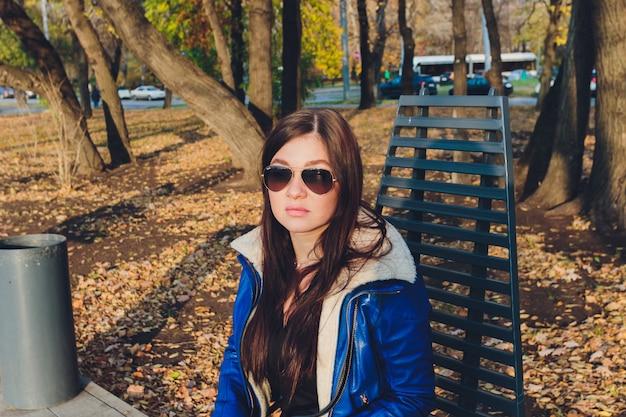Piękna dziewczyna siedzi na ławce w parku na tle zieleni.