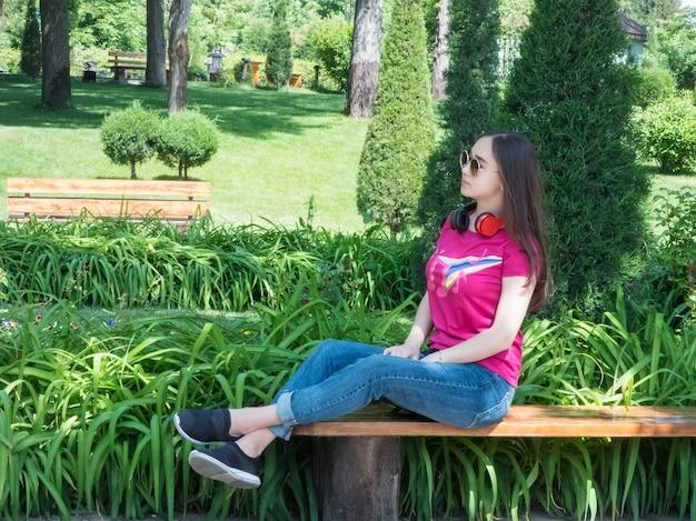 Piękna dziewczyna siedzi na ławce w zielonym parku, słoneczny dzień. dziewczyna o azjatyckim wyglądzie