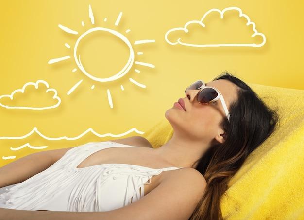 Piękna dziewczyna siedzi na leżaku na plaży na żółtym tle