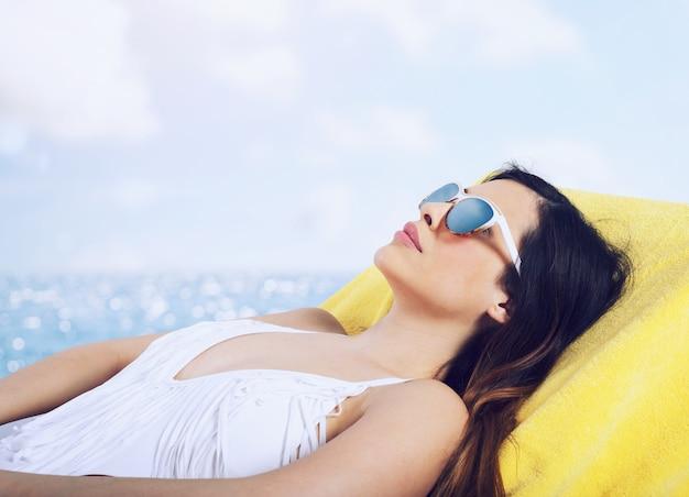 Piękna dziewczyna siedzi na leżaku na plaży