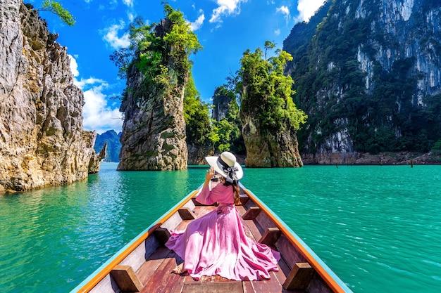 Piękna dziewczyna siedzi na łodzi i patrząc na góry w ratchaprapha dam w parku narodowym khao sok, prowincja surat thani, tajlandia.