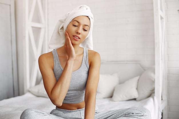 Piękna dziewczyna siedzi na łóżku przy użyciu produktów kosmetycznych