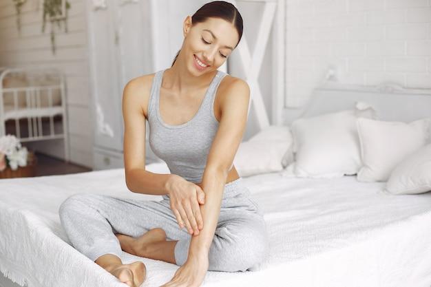 Piękna dziewczyna siedzi na łóżku z kosmetykami