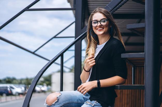 Piękna dziewczyna siedzi na metali schodkach na drewnianym tle dom z pionowo deskami z długie włosy i szkłami. kobieta uśmiechnięta i patrzeje kamerę