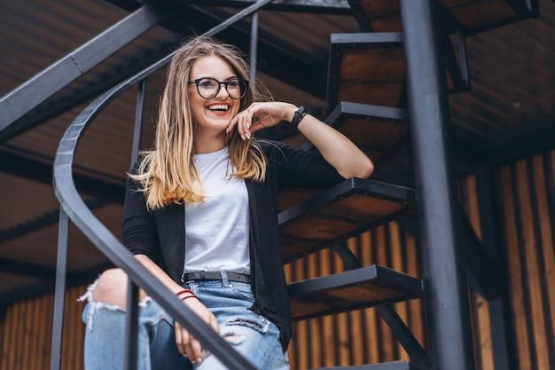 Piękna dziewczyna siedzi na metali schodkach na drewnianym tle dom z pionowo deskami z długie włosy i szkłami