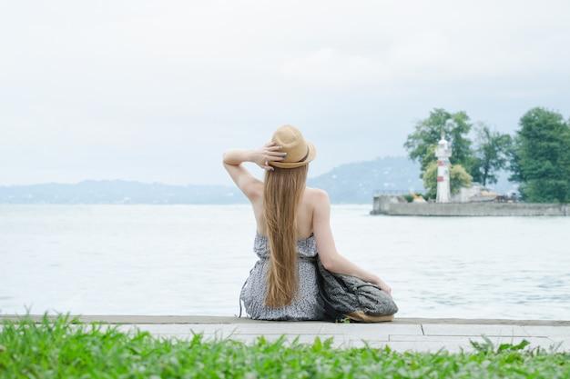 Piękna dziewczyna siedzi na molo