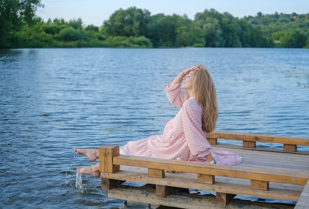 Piękna dziewczyna siedzi na moście nad brzegiem rzeki