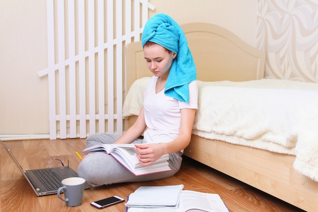Piękna dziewczyna siedzi na podłodze i pracuje przy komputerze.